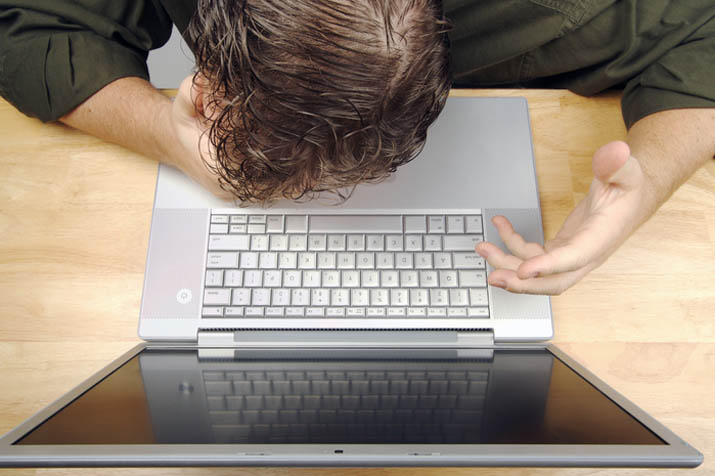 Businessman shows his frustration while working on his laptop.